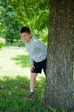 Een jongen speelt in het park Stock Afbeelding