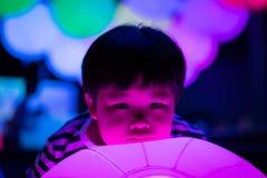 Een jongen speelt kleurrijke lichte ballen Royalty-vrije Stock Afbeelding