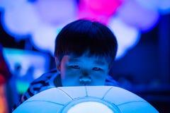 Een jongen speelt kleurrijke lichte ballen Stock Fotografie