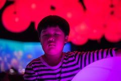 Een jongen speelt kleurrijke lichte ballen Royalty-vrije Stock Afbeeldingen