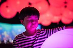 Een jongen speelt kleurrijke lichte ballen Royalty-vrije Stock Foto's