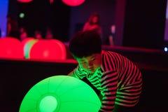 Een jongen speelt kleurrijke lichte ballen Stock Foto