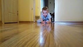 Een jongen speelt met auto op de vloer stock video