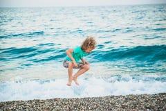 Een jongen speelt met de overzeese golven Stock Foto
