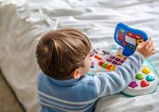 Een jongen speelt met een muzikaal stuk speelgoed op het bed van zijn ruimte stock foto
