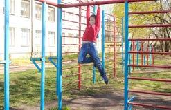Een jongen speelt in openlucht op de speelplaats Stock Foto