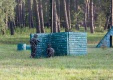 Een jongen speelt paintball op het gebied twee teams van paintballspelers in camouflage vormen zich met maskers, helmen, kanonnen royalty-vrije stock fotografie
