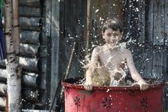 Een jongen speelt in water Stock Fotografie