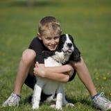 Een jongen stelt met zijn puppy Stock Foto's