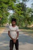 Een jongen stelt voor een foto terwijl het hoeden van vee buiten Bhadarsa stock fotografie