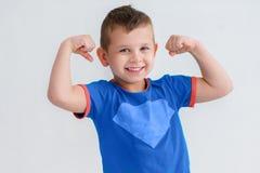 Een jongen toont de spieren in haar wapens Royalty-vrije Stock Foto