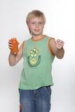 Een jongen van elf jaar houdt in handen inpakkend met vitaminen. Royalty-vrije Stock Foto