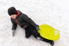 Een jongen van zeven jaar het oude liggen op de sneeuw en het houden van een groene plastic slee in zijn hand Concept de winterac royalty-vrije stock foto