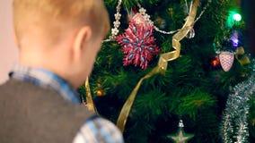 Een jongen verfraait een Kerstboom stock footage