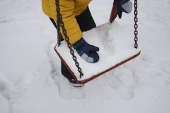 Een jongen verzamelt sneeuw met een schommeling in het park royalty-vrije stock afbeelding