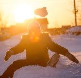Een jongen werpt sneeuw in de hemel bij zonsondergang royalty-vrije stock foto