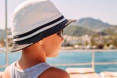 Een jongen in een witte hoed die het overzees bekijken De zomer stock fotografie