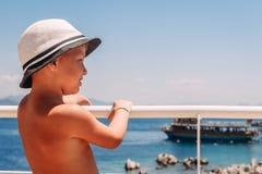 Een jongen in een witte hoed die het traliewerk op het schip houden en het overzees bekijken stock afbeelding