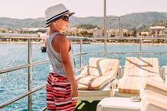 Een jongen in een witte hoed en borrels die het traliewerk op het schip houden en het overzees bekijken stock foto's
