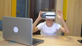 Een jongen in witte kleren zit bij een lijst en speelt in virtuele glazen stock videobeelden