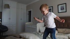 Een jongen in een witte T-shirt springt op het bed en lacht bij het gezicht van zeepbels in de ouders` slaapkamer in langzame mot stock video