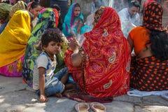 Een jongen zit met Hindoese vrouwen in traditionele Sari bij Durbar-Vierkant Stock Afbeeldingen