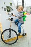 Een jongen zit op een fiets Stock Afbeelding