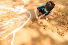 Een jongen in zwemmend kostuum zit op het het strand en het spelen zand Stock Foto