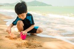 Een jongen in zwemmend kostuum zit op het het strand en het spelen zand Stock Foto's