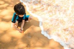 Een jongen in zwemmend kostuum zit op het het strand en het spelen zand Royalty-vrije Stock Foto's