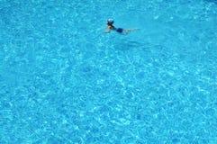 Een jongen zwemt in blauw duidelijk water Stock Afbeeldingen