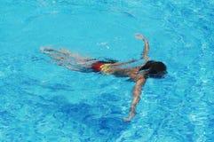 Een jongen zwemt in blauw water Stock Fotografie