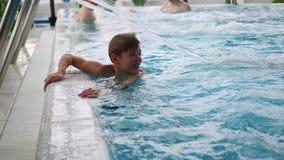 Een jongen zwemt in de pool Ontspanning en pret in de pool stock videobeelden