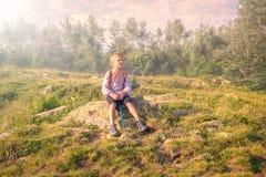 Een jongensreiziger met een rugzak en trekkingspolen rust op een steen in de mist royalty-vrije stock foto