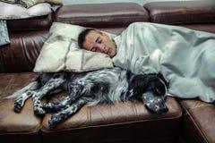Een jongensslaap met zijn hond stock foto