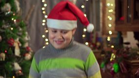 Een jongenstiener in een hoed Santa Claus danst dichtbij de Kerstboom Kerstmisvakantie, gelukkig nieuw jaar stock video
