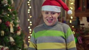 Een jongenstiener in een hoed Santa Claus danst dichtbij de Kerstboom Kerstmisvakantie, gelukkig nieuw jaar stock footage