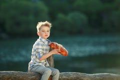 Een Jongenstribune dichtbij Houten Omheining in een willage stock fotografie