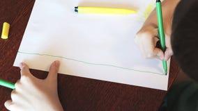 Een jongenszitting bij bureau en het schilderen schetsen met kleurrijke teller op Witboek stock video
