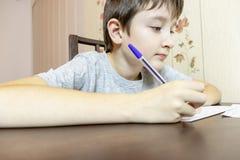 Een jongenszitting door de lijst thuis en schrijvend met een pen op papier royalty-vrije stock fotografie