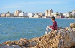 Een Jongenszitting op een Rots Stock Afbeeldingen