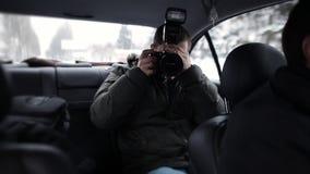 Een journalist die in een taxi met een in hand camera reizen en controleert de flitsverrichting stock videobeelden