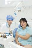 Een juffrouwtandarts en haar patiënt in kliniek Royalty-vrije Stock Foto