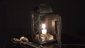 Een kaars brandt in de oude lamp, op een zwarte achtergrond stock video
