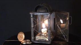 Een kaars brandt in de oude lamp, op een zwarte achtergrond stock footage