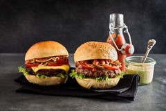 Een kaashamburger op een duidelijk broodje naast onderdompeling Stock Foto's