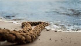 Een kabel bij de rand van het water bij een strand Stock Fotografie