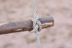 Een kabel is gebonden in een knoop rond een omheiningspost, kabel gebonden knoop wo Stock Afbeeldingen
