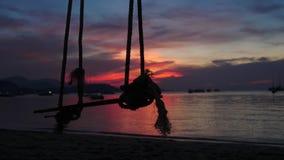 Een kabelschommeling hangt van een boom dichtbij het overzees tijdens mooie zonsondergang Langzame Motie 3840x2160 stock video