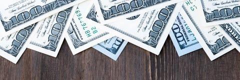 Een kader van honderd dollarsrekeningen bij de bovenkant en een achtergrond van donker hout royalty-vrije stock afbeeldingen